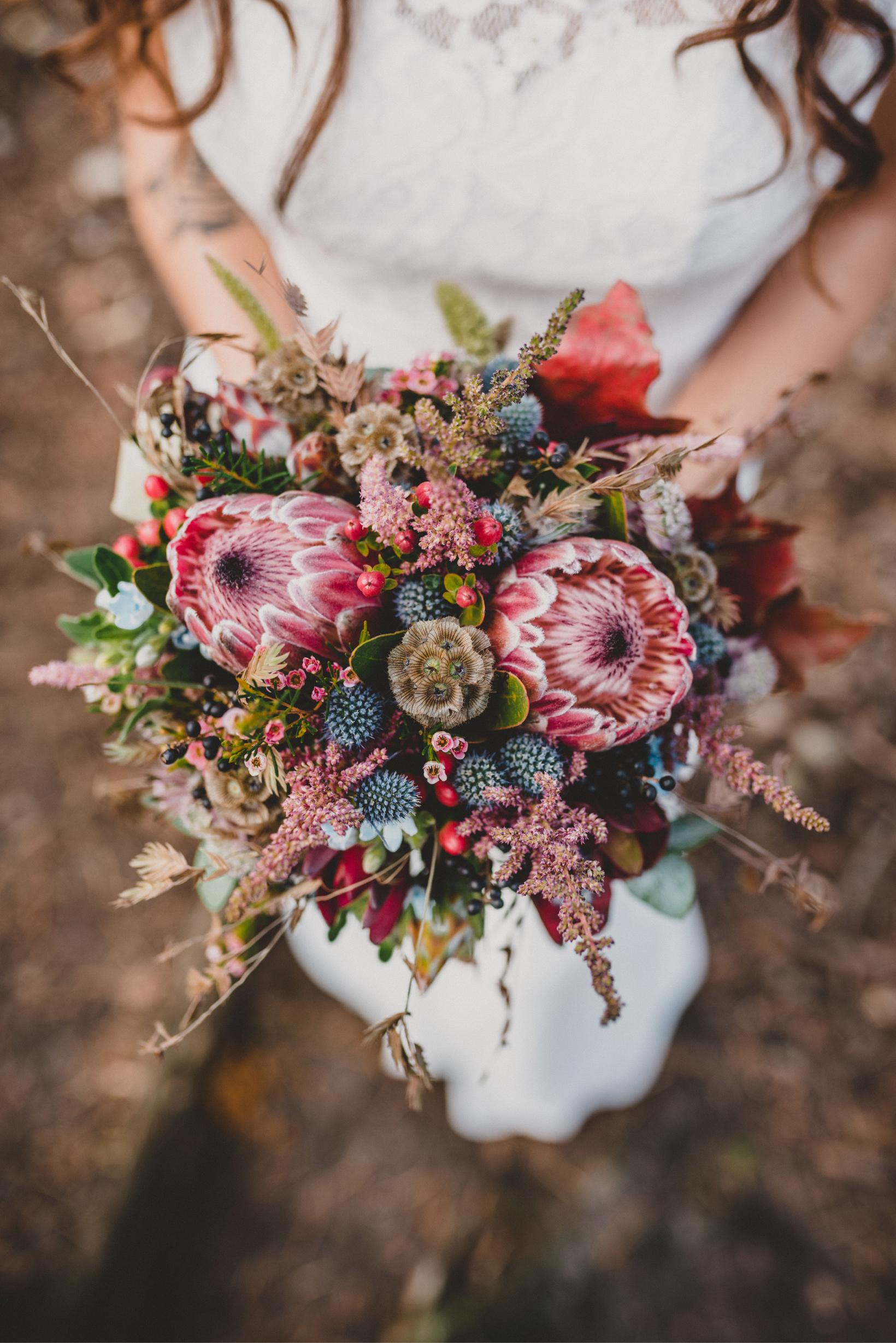 woman holding protea bouquet